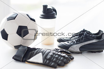 close up of football boots, gloves and bottle