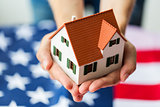 close up of hands holding house over american flag