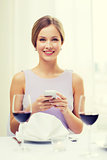 smiling woman with smartphone at resturant