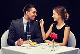 smiling couple eating dessert at restaurant