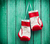 pair of red boxing gloves hanging on a nail on a background of g