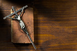 Silver Crucifix and Holy Bible on Wooden Background