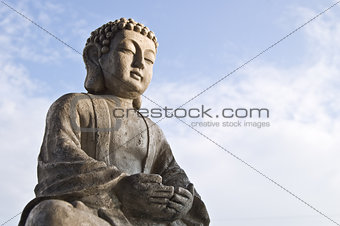 Sitting Buddha image in lotus position on sky background.