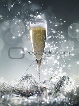 One champagne glass and silver decoration on a silver shiny glit