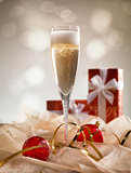 Christmas glasses of Champagne and golden background with red gi
