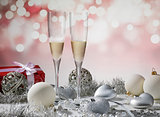 two glasses of champagne for christmas celebration with red deco