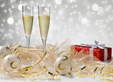 Two champagne glasses, golden decoration. Red gift with white ri