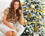 Thoughtful young woman sitting near christmas tree