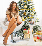 Full length portrait of happy young woman sitting near christmas