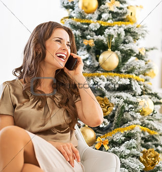 Portrait of happy young woman talking cell phone while sitting n