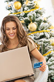 smiling young woman with credit card using laptop near christmas