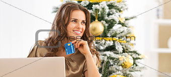 Portrait of thoughtful young woman with credit card using laptop