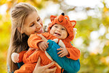 Young woman and her baby son in autumn park, boy dressed in fox costume