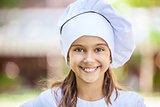 Smiling girl in a chef's hat