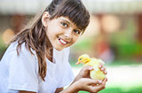 Smiling girl with a spring duckling