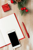 Christmas composition with notebook, gift and smartphone