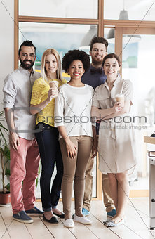 happy smiling creative team with coffee in office