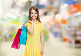 smiling girl with shopping bags over supermarket