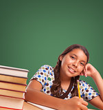Cute Hispanic Girl StudyingIn Front of Blank Chalk Board