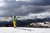 Happy young skier with ski poles in sun mountains and cloudy gra