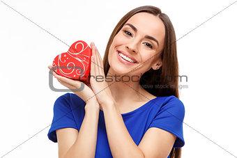 Beautiful woman holding heart shaped gift