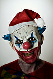 scary evil clown with a santa hat