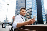happy man with smartphone and bicycle in city