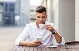 man with smartphone drinking coffee at city cafe