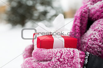 close up of woman holding christmas gift outdoors