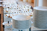a stack of white plates on banquet table