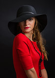 The beautiful young girl in a bright red dress and  black hat with the wide fields