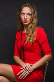 The beautiful young girl in a bright red dress
