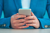 Businesswoman using smartphone, close up of hands