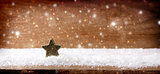 Christmas wooden background with star and snowfall.