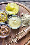 Different kinds of mustard on the wooden background