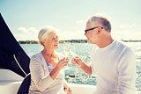 senior couple clinking glasses on boat or yacht