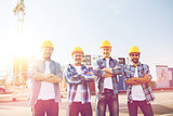 group of smiling builders in hardhats outdoors