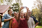 friends taking selfie at party in summer garden