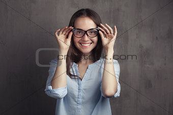 portrait of smiling woman with glasses near grey background wall