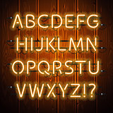 Glowing Neon Alphabet on Wooden Background