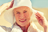 happy senior woman in sun hat on summer beach