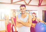 smiling man standing in front of the group in gym
