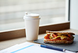 salmon panini sandwich and cup of drink at cafe