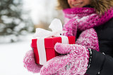 close up of woman with christmas gift outdoors