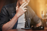 man drinking beer and smoking cigarette at bar