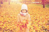 smiling little girl with autumn leaves in park