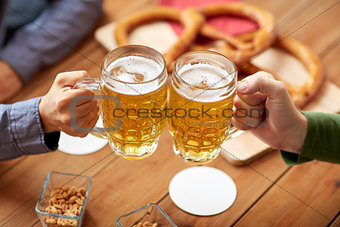 close up of hands clinking beer mugs at bar or pub