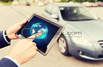 close up of male hands with tablet pc and car