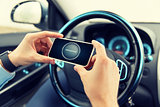 hands with navigator on smartphone in car