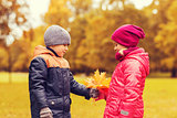 little boy giving autumn maple leaves to girl